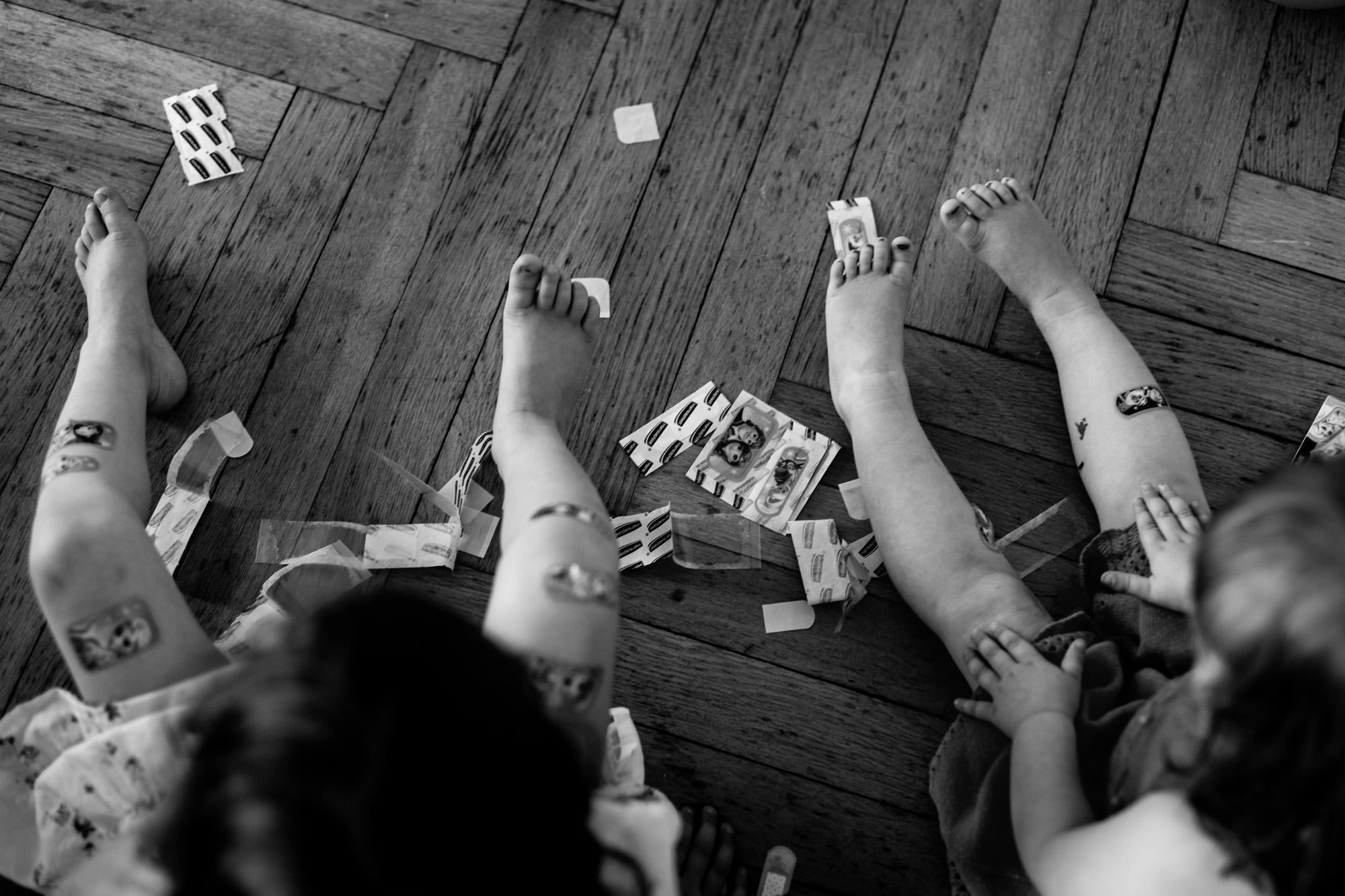 Beine zweier Mädchen mit vielen Pflastern.