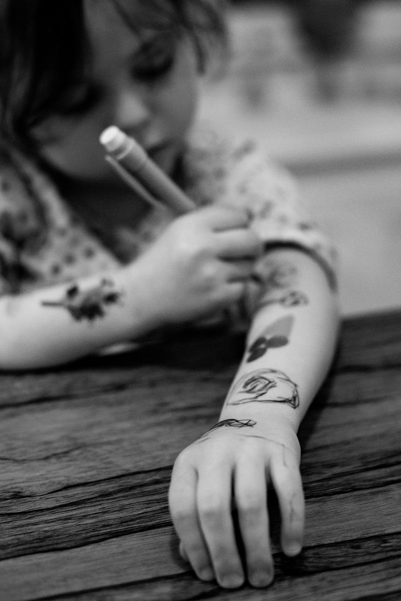 Ein Kind schreibt mit Kugelschreiber auf seinem Arm.