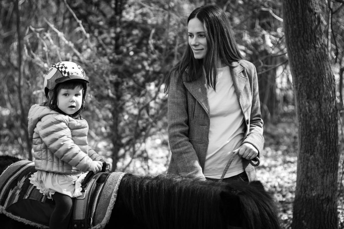 Mädchen auf einem Pferd mit Mutter.