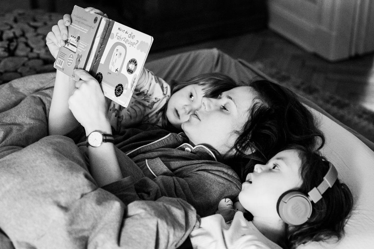 Mutter liest ihren Töchtern im Bett vor.