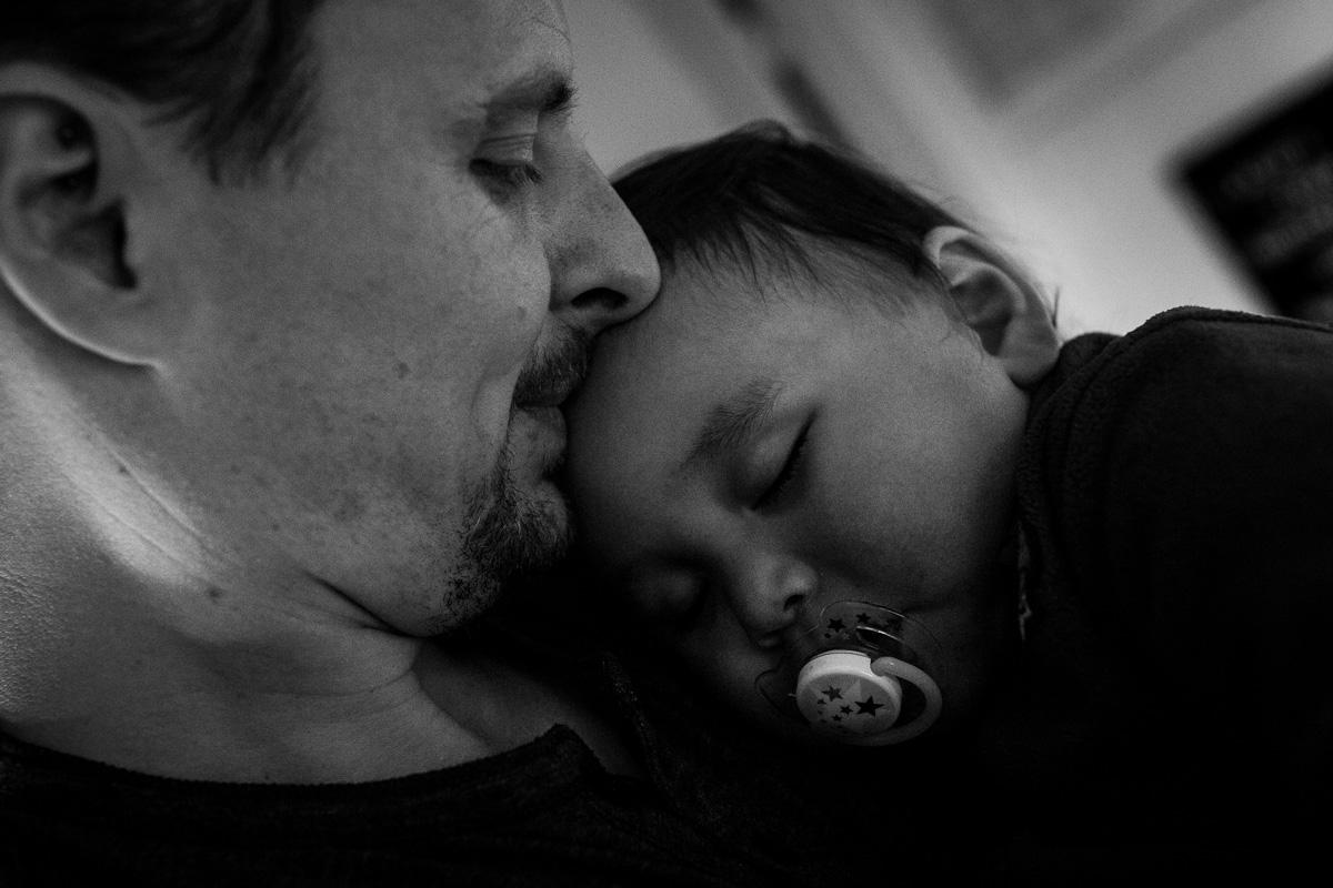 Familienreportage. Sohn schläft auf der Schulter von seinem Vater.