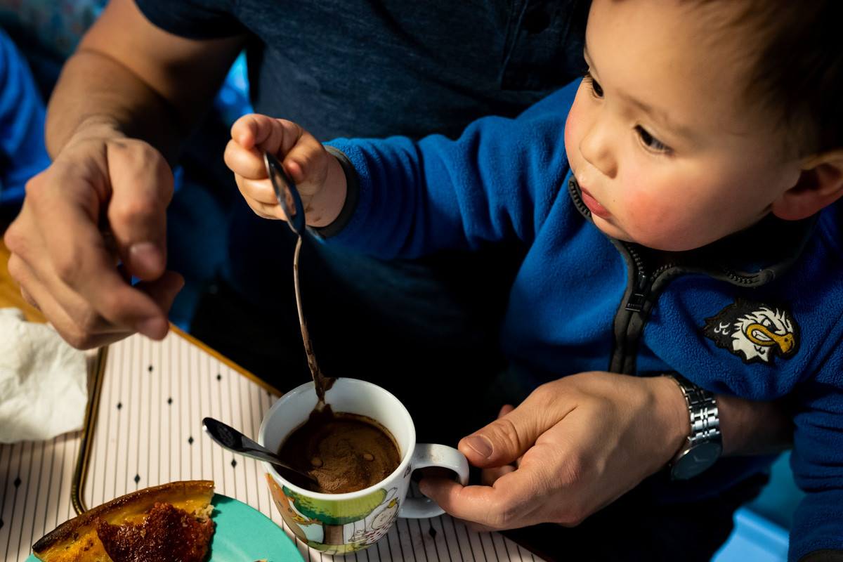 Famililienreportage. Ein kleiner Junge schaut sich sein Spiegelbild in einem Löffel an.
