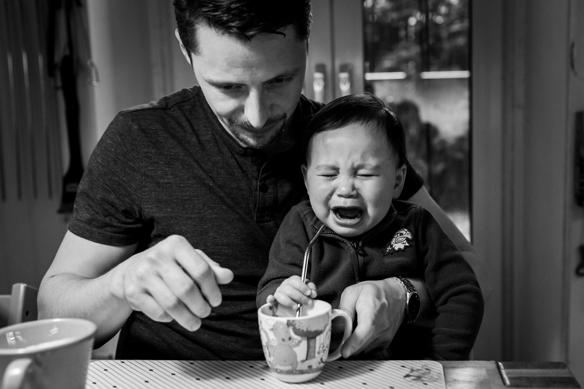Alltag einer Familie: Vater und der kleine weinende Sohn.