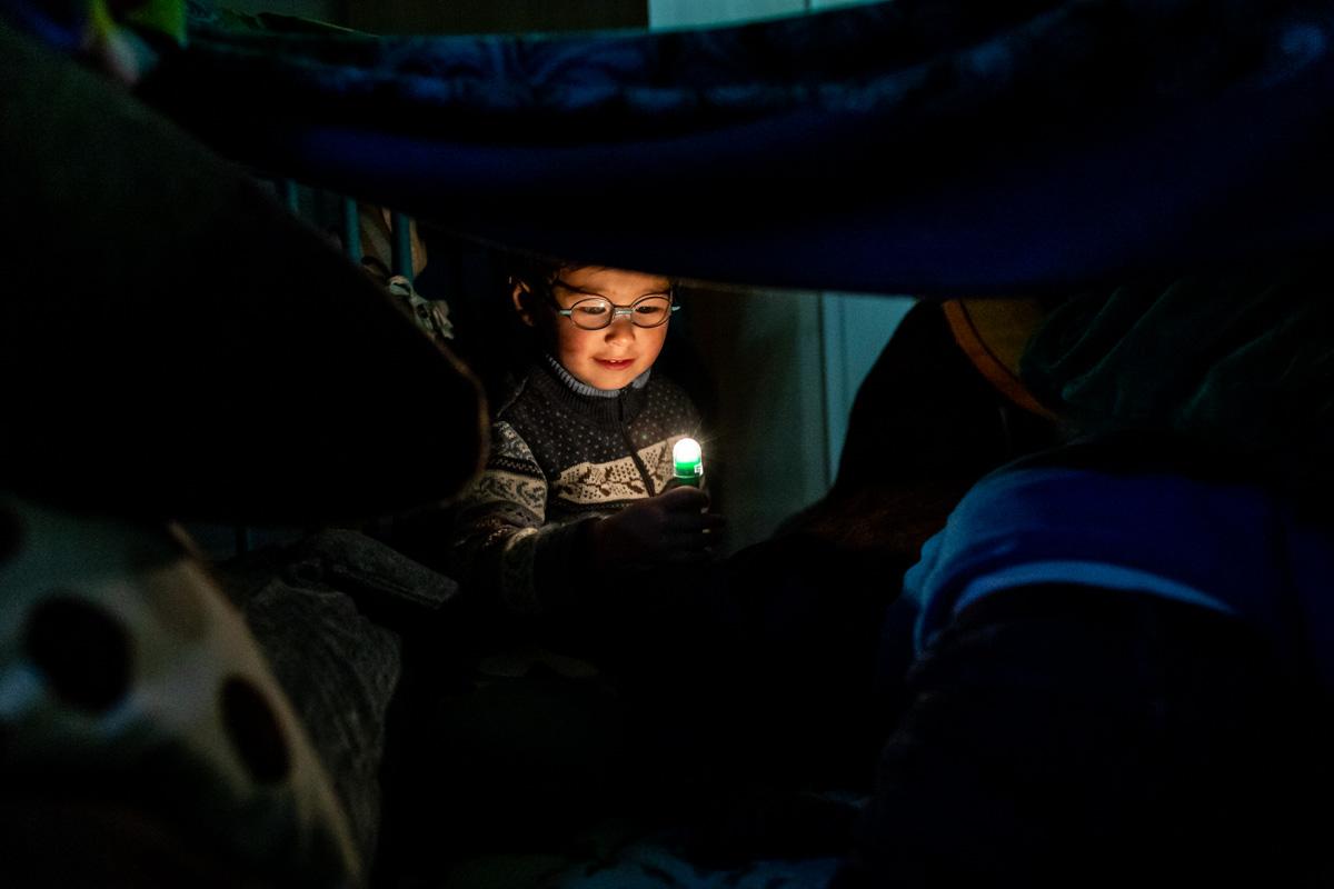 Dokumentarische Familienfotografie. Ein Junge mit Taschenlampe.