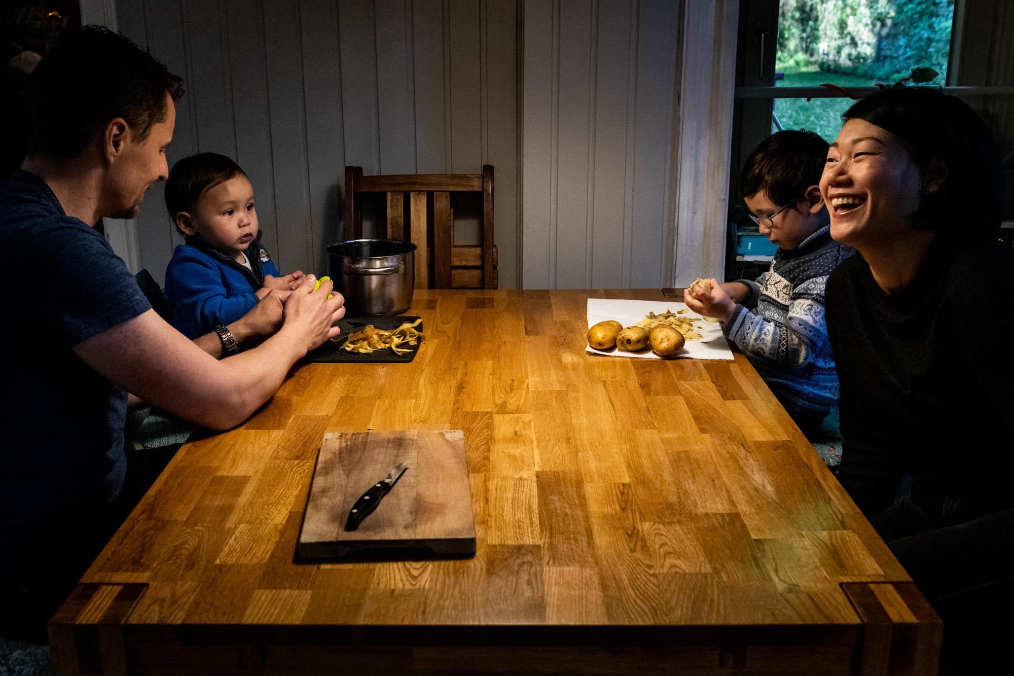 Eine Familie sitzt zusammen an einem Tisch in der Küche, Kinder schälen Kartoffeln.