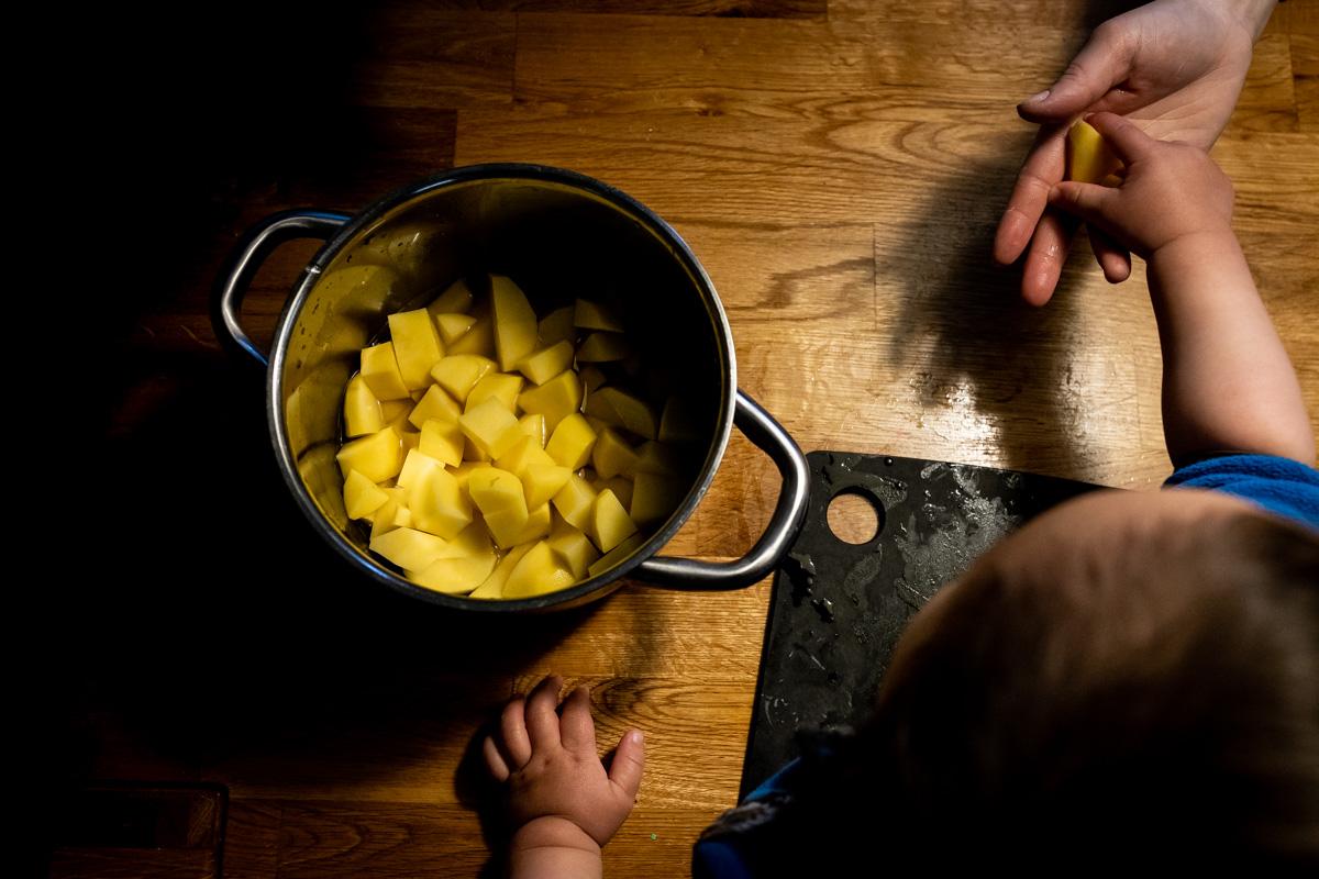 Familienmoment. Ein Topf mit Kartoffeln und eine kleine Kinderhand.