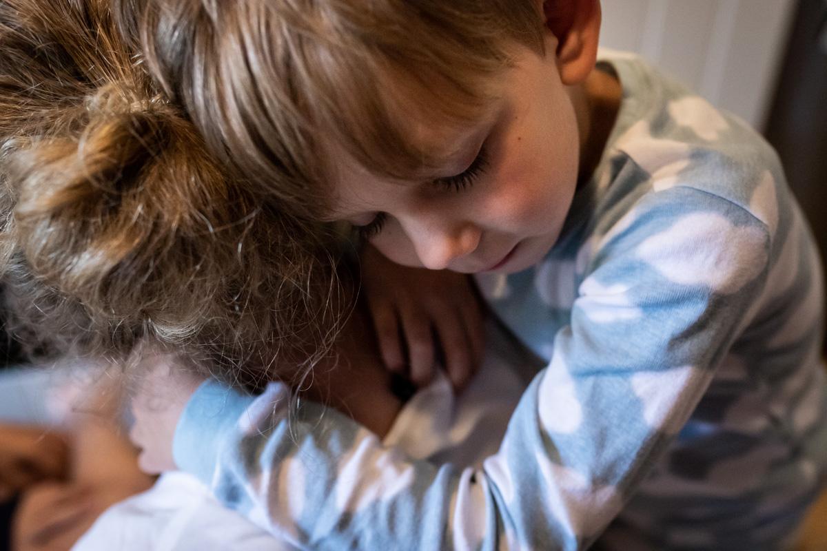 Ein Junge lehnt sich an den Kopf seiner Mutter.