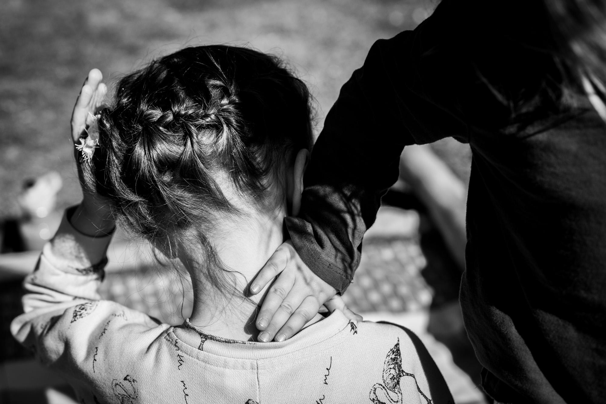Familienmoment. Eine kleine Hand berührt den Hals eines Mädchens.