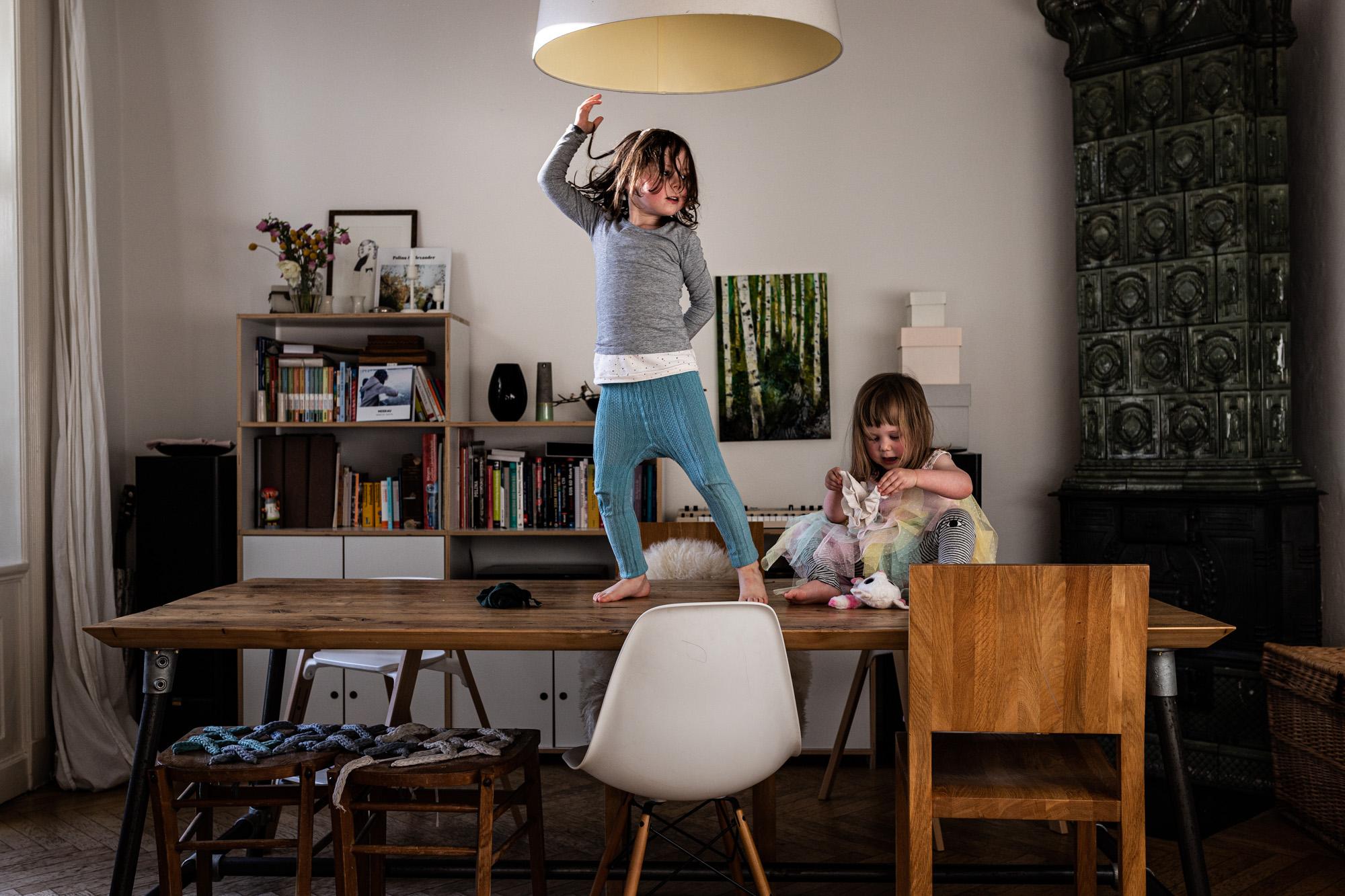 Familienreportage. Mädchen tanzt auf dem Tisch.