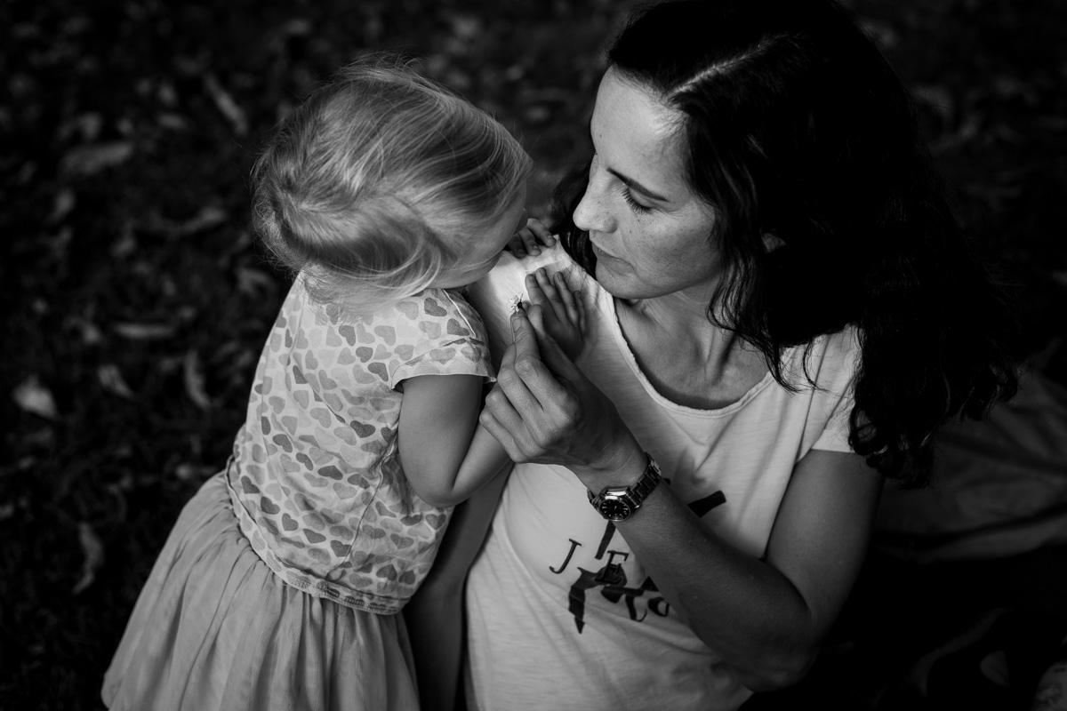 Mutter und Tochter betrachten eine kleine Blume.