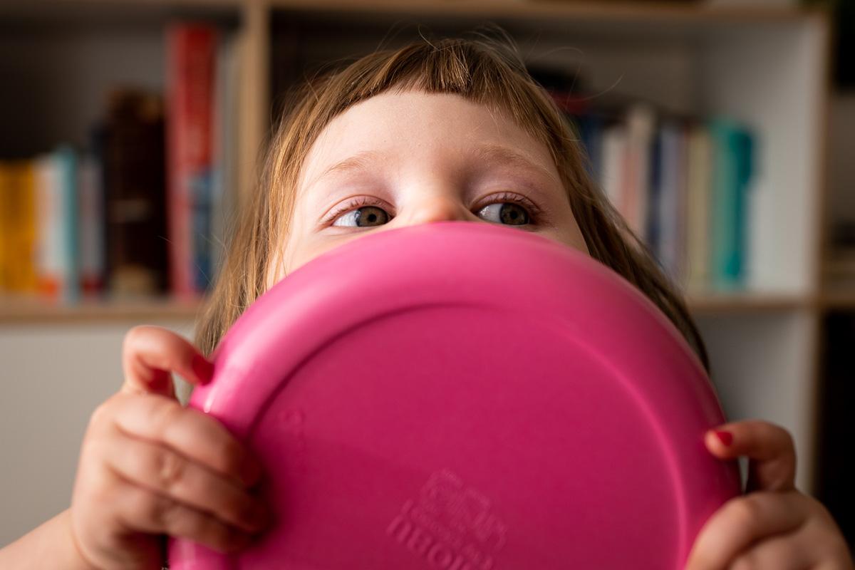Familienfotografie Hamburg: Mädchen leckt einen Teller ab.