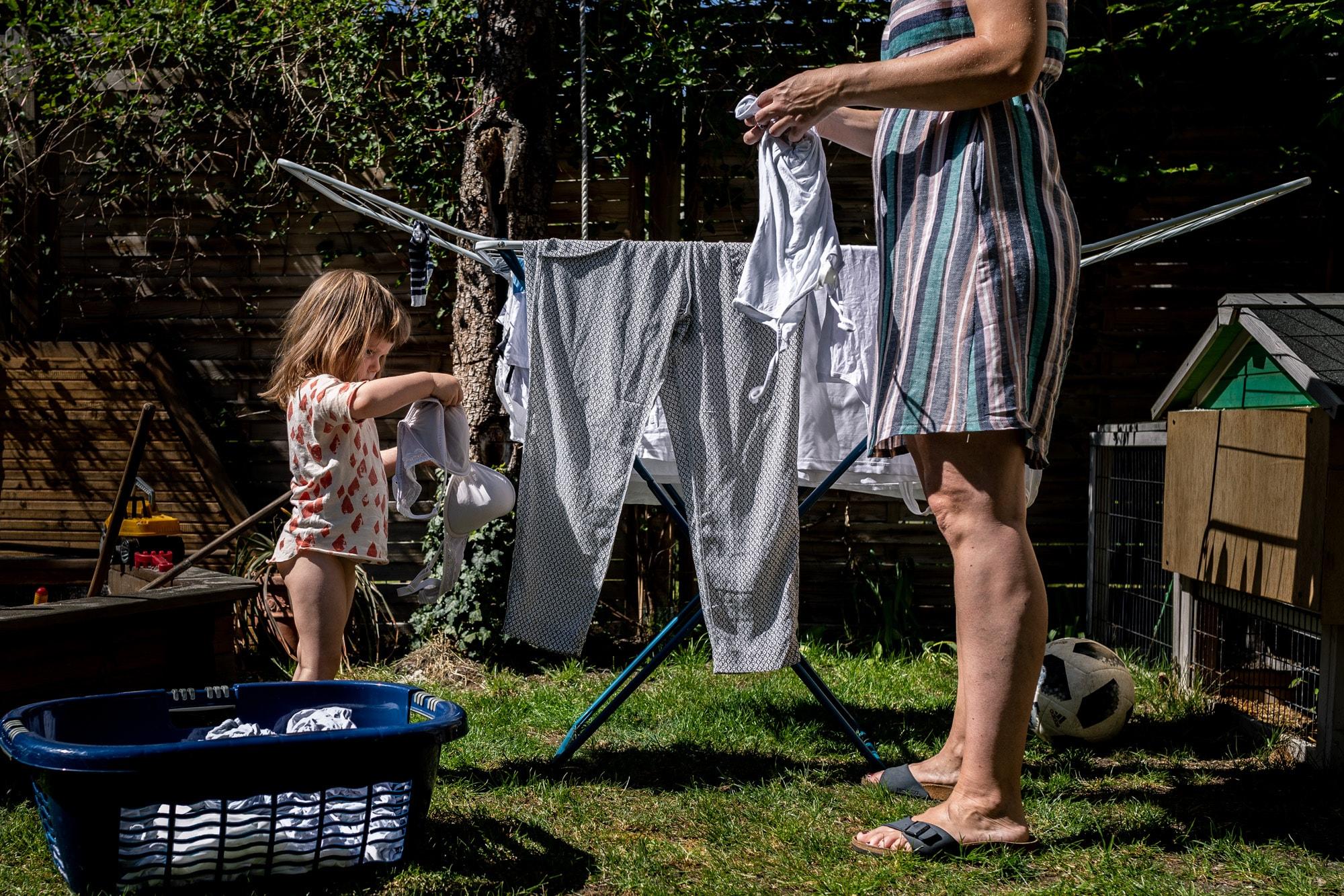 Ein Mädchen und eine Frau hängen zusammen Wäsche auf.
