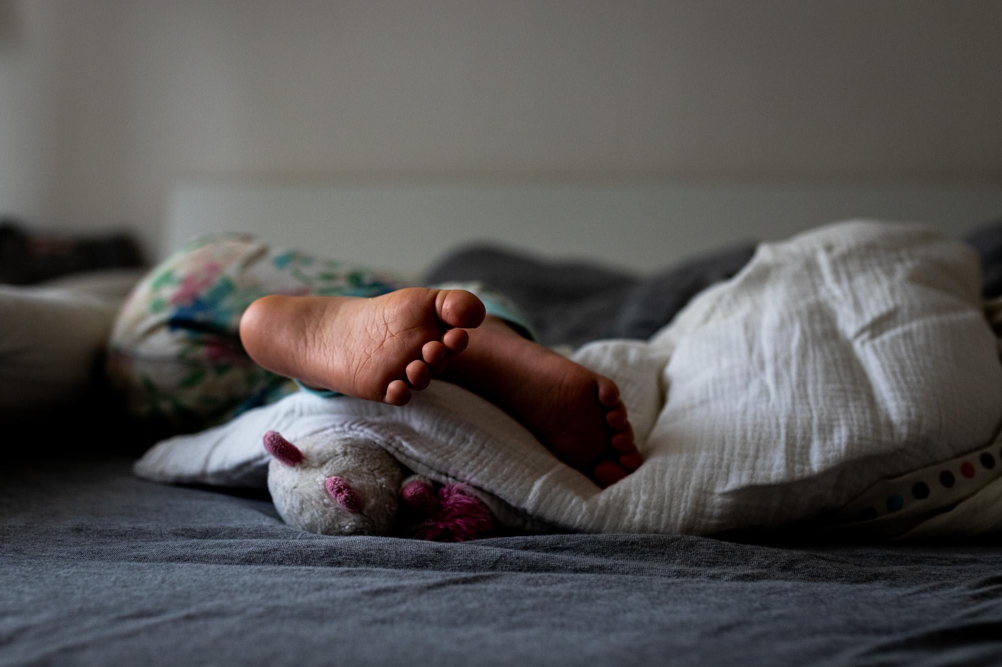 Familienbild. Kinderfüße im Bett.