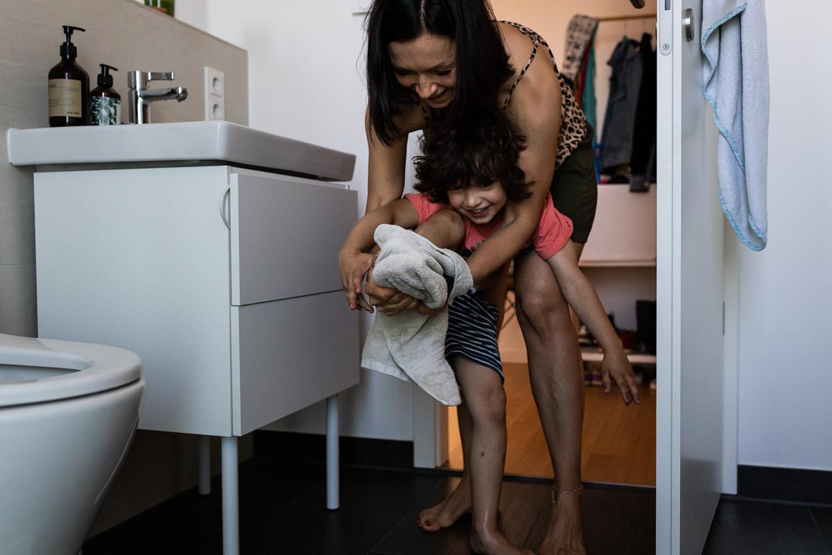 Echtes Leben. Mutter trocknet die Füße ihres Sohnes ab.