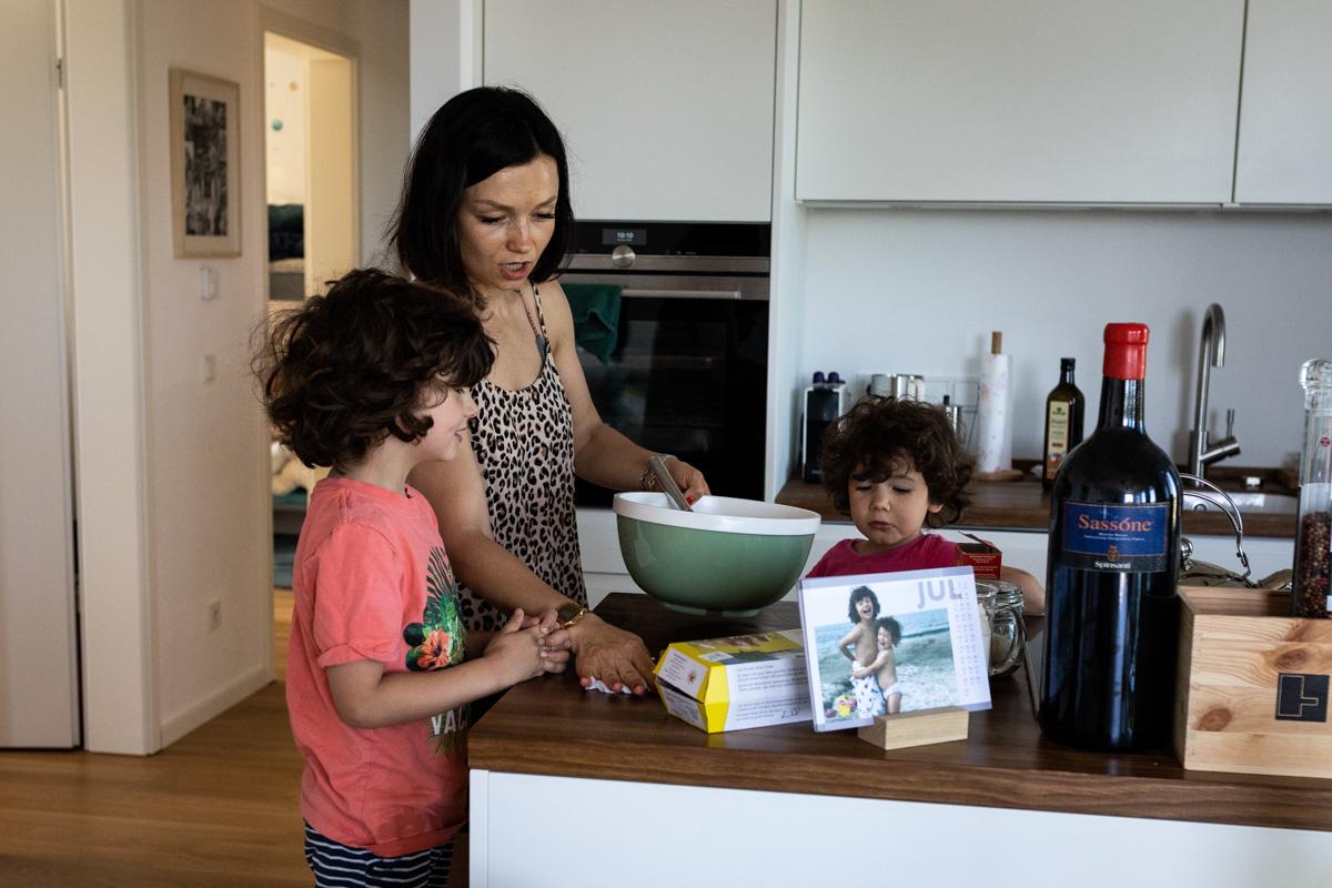 Familiendokumentation. Mutter kocht mit ihren Kindern.