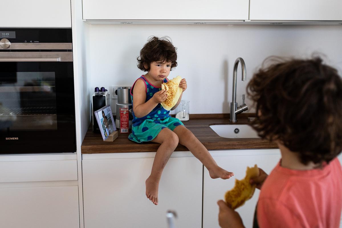 Mädchen sitzt und isst einen Pfannkuchen.
