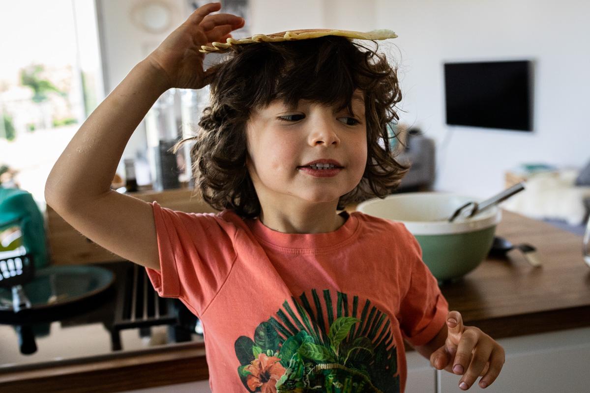 Ein Junge mit einem Pfannkuchen auf dem Kopf.