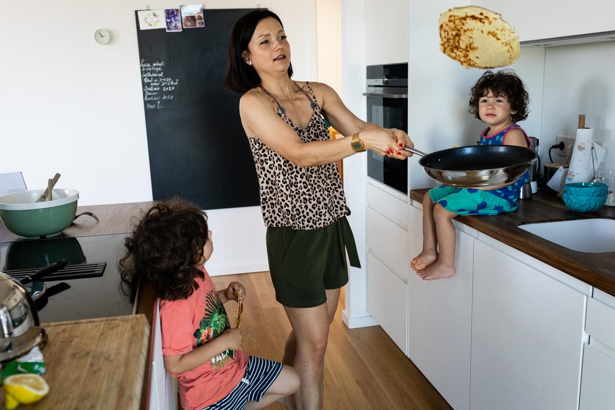 Familienfoto in der Küche. Mutter wirft einen Pfannkuchen hoch.