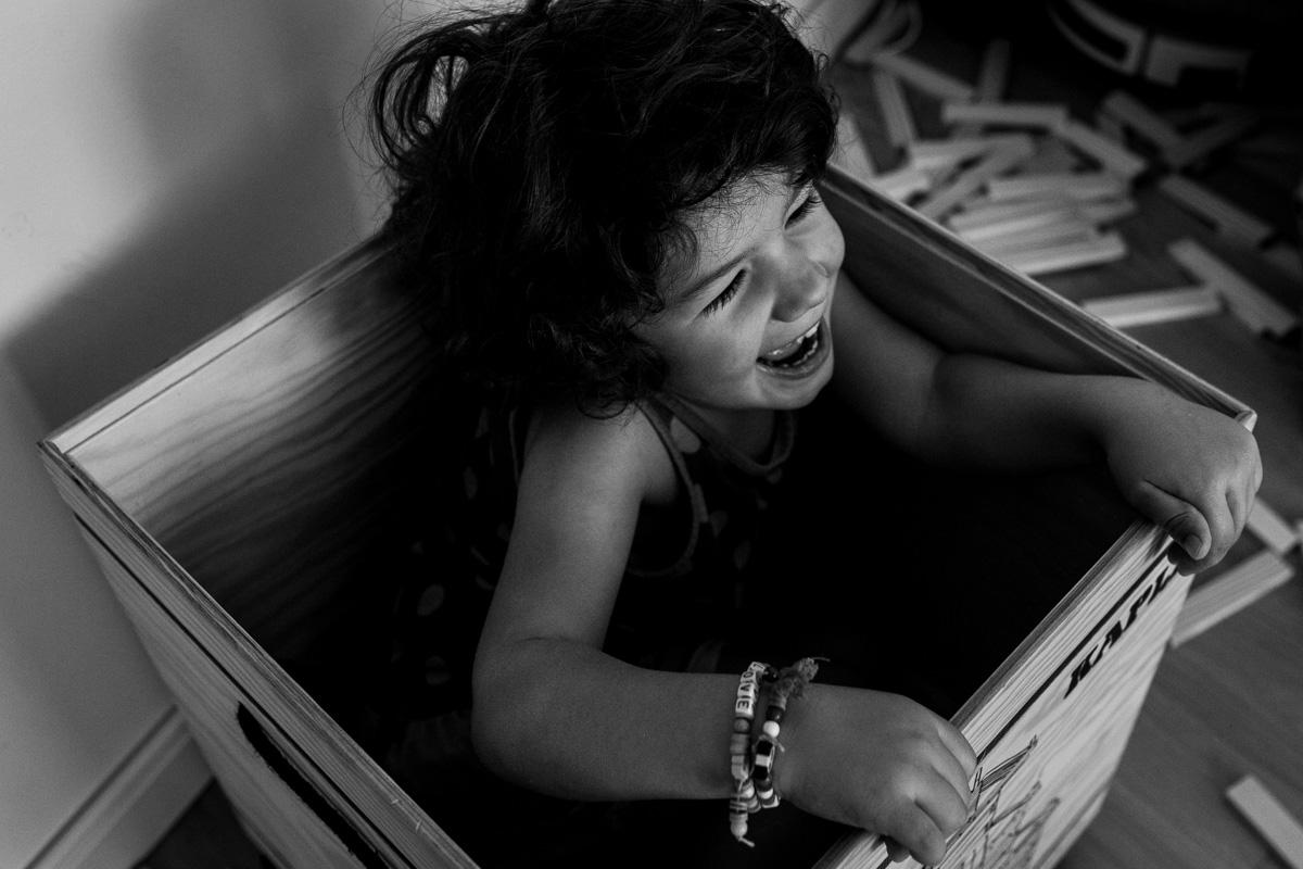 Ein Mädchen sitzt in einer Kiste und lacht.