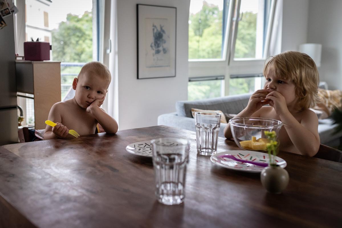 Zwei Brüder am Frühstückstisch. Der kleinere Bruder wartet auf sein Essen.