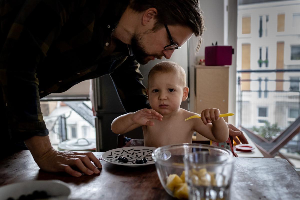 Kleiner Junge am Frühstückstisch, Vater beugt sich zu ihm.