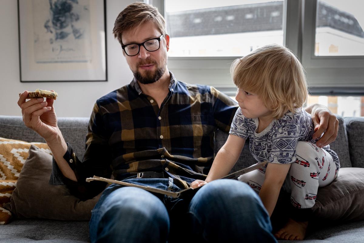 Vater und Sohn auf der Couch. Vater hält ein Brot in der Hand und hat ein Buch auf seinem Schoß.