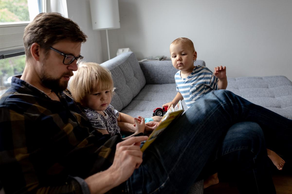 Ein Vater liest seinem Sohn ein Buch vor. Der kleinere Bruder schaut neugierig.