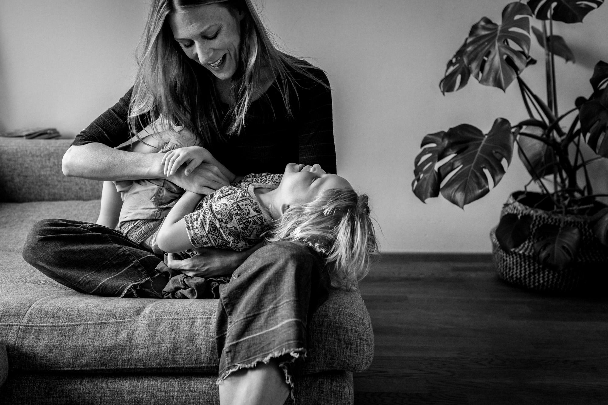 Familienfoto. Mutter kitzelt ihren Sohn, beide lachen.