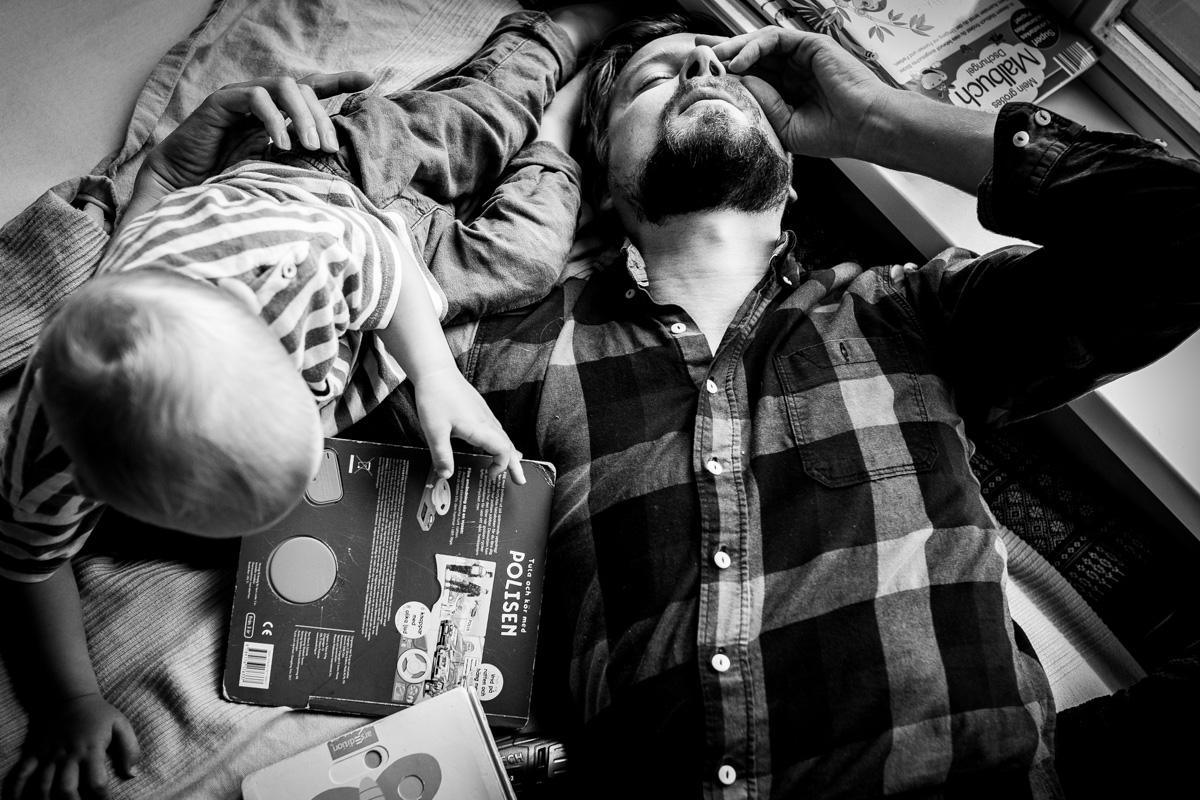 Ein Vater erschöpft mit seinem Sohn auf dem Bett.