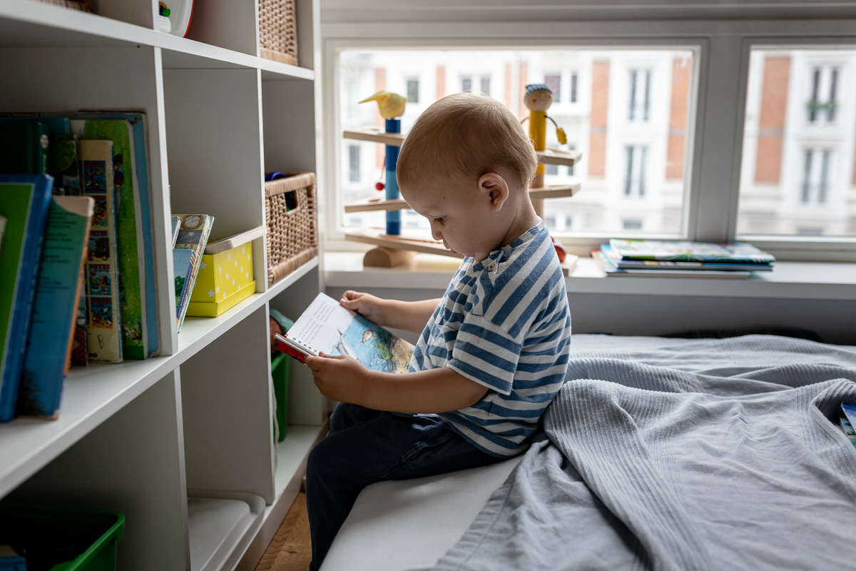 Ein kleiner Junge schaut sich ein Buch an.
