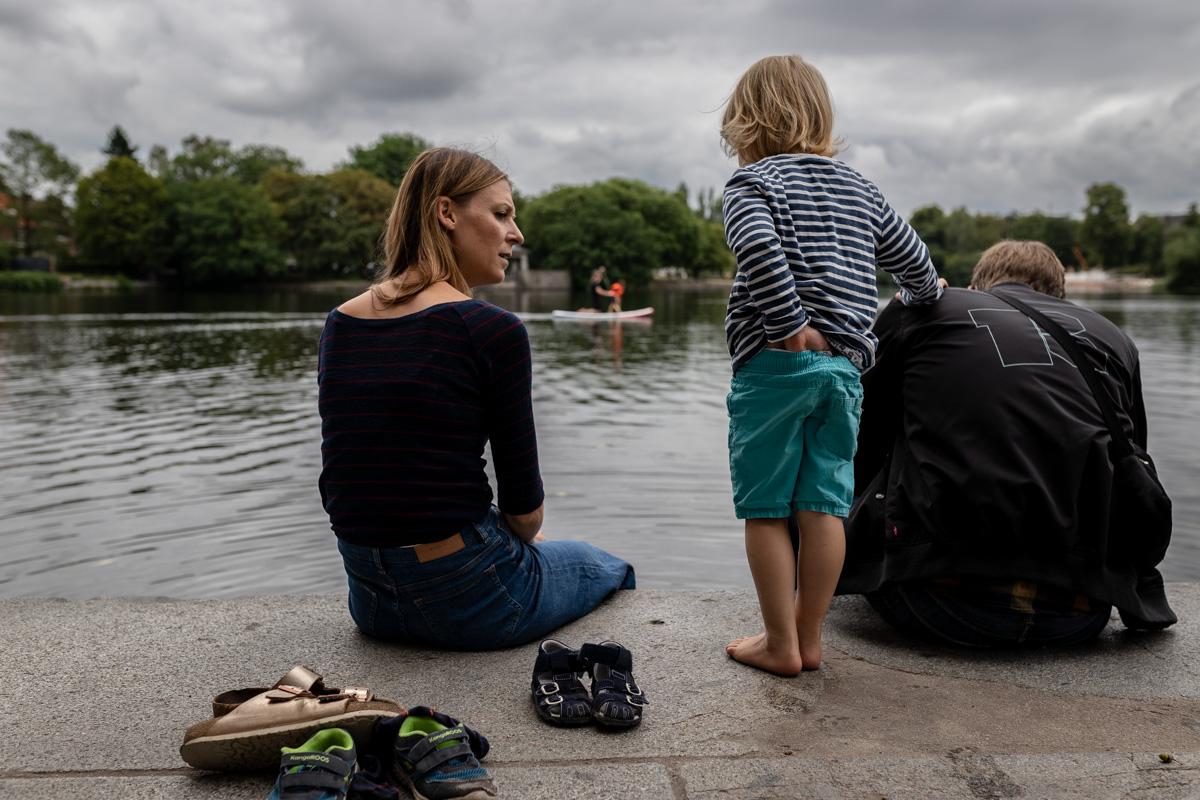 Familie sitzt am Wasser. Der Junge steht und hält sich an seinem Vater fest.