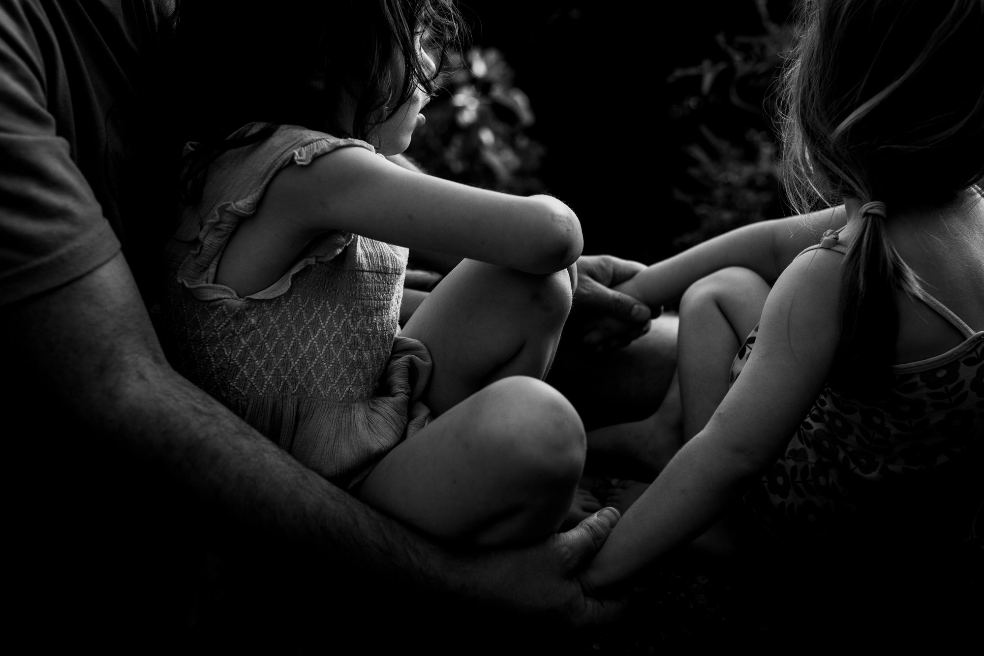 Hände und Arme. Ein Mann hält seine Töchter fest. Ein sehr zärtliches Bild.