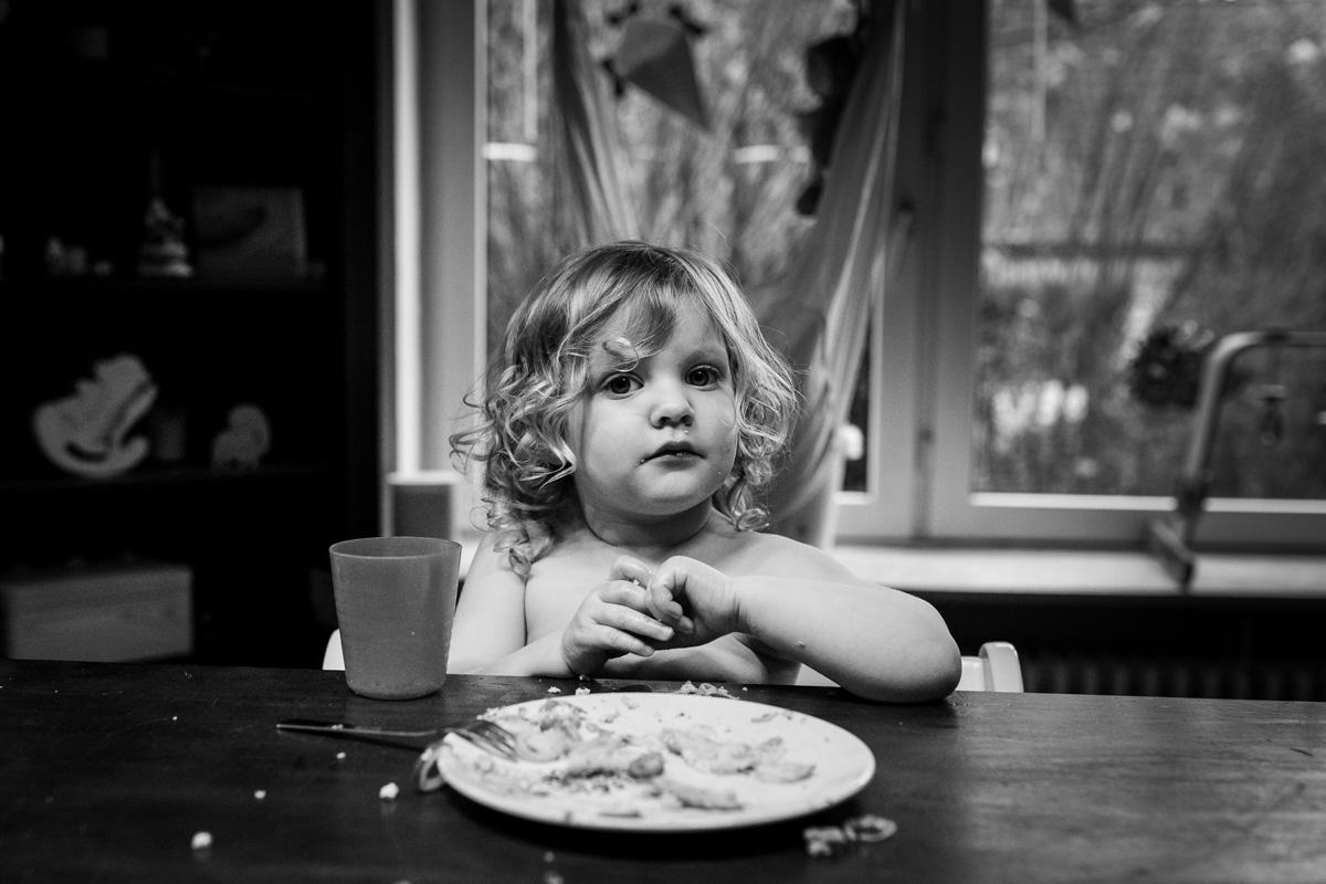 Ein kleines Mädchen sitzt am Esstisch.