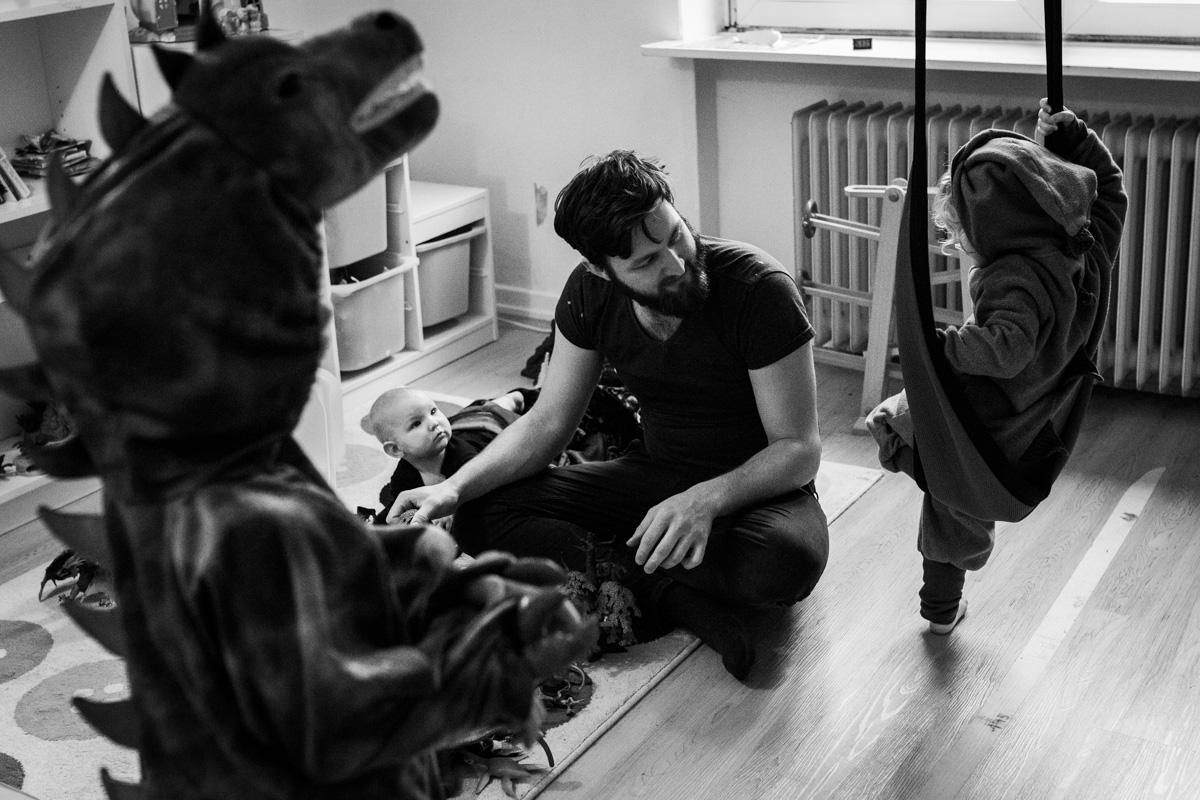 Eine Familie im Kinderzimmer. Ein kleines Mädchen schaukelt. Im Vordergrund steht ein Junge im Dinosaurier-Kostür. Auf dem Boden sitzt Vater mit Baby.