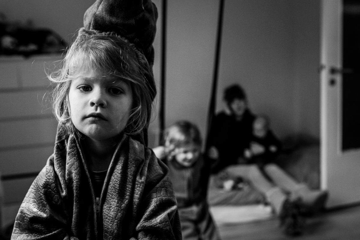 Ein Kind mit einem direkten Bick in die Kamera, im Hintergrund seine Familie