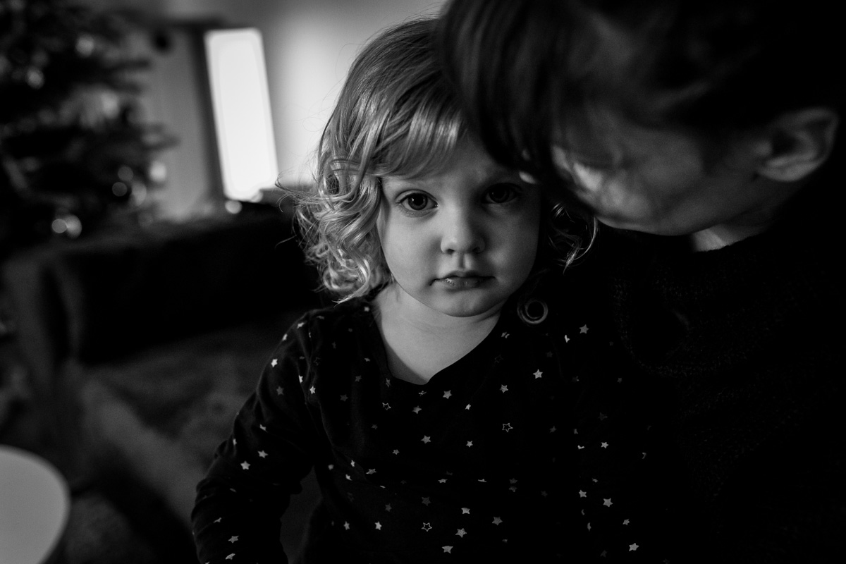 Mädchen auf dem Schoß seiner Mutter. Das Mädchen schaut den Betrachter an