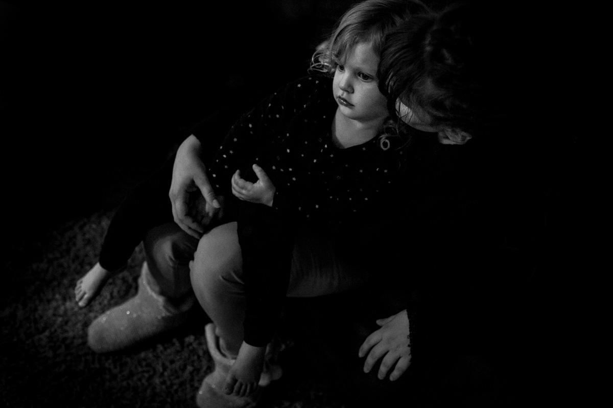 Mutter hält zärtlich ein kleines Mädchen auf ihrem Schoß