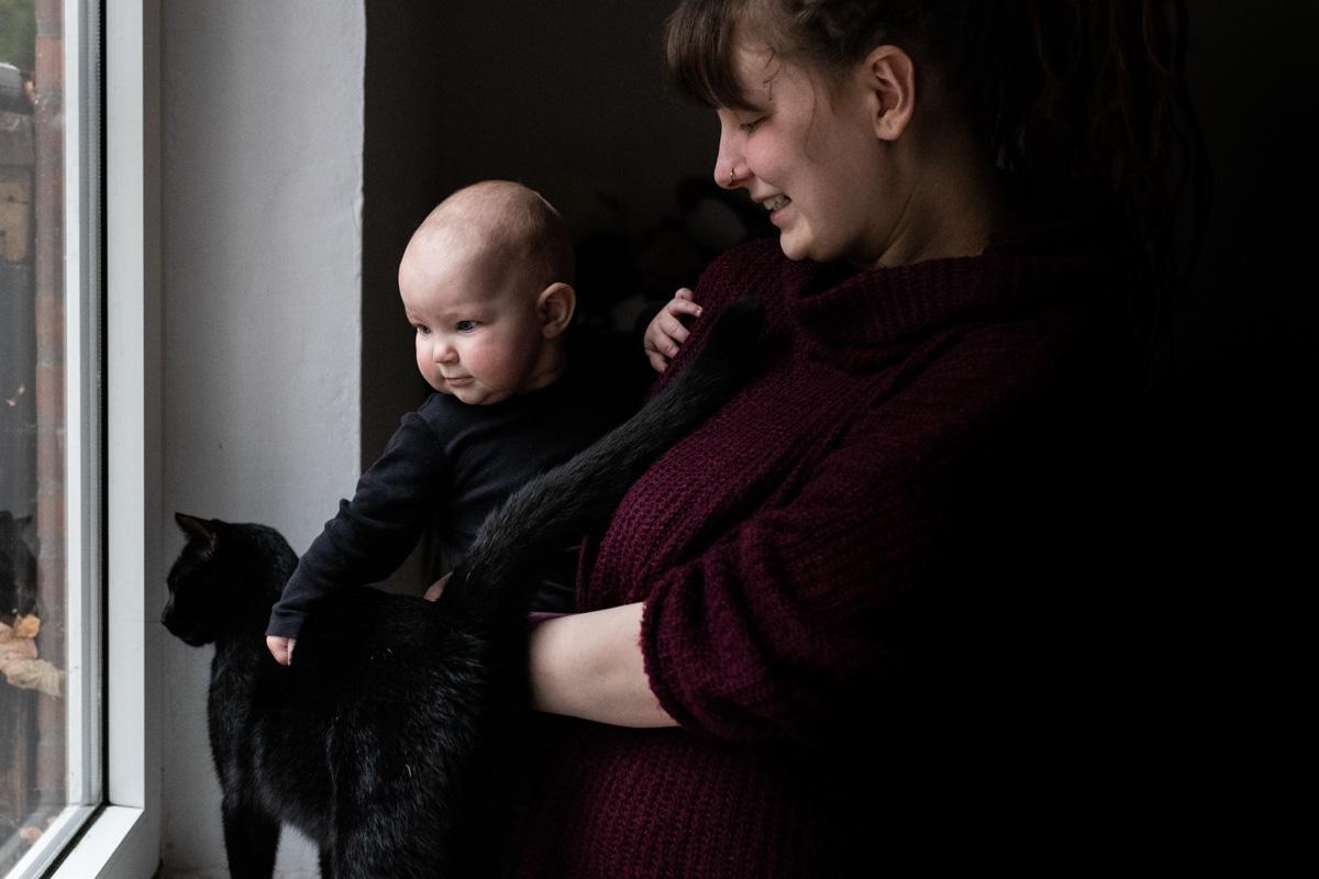 Mutter mit Baby und Katze am Fenster