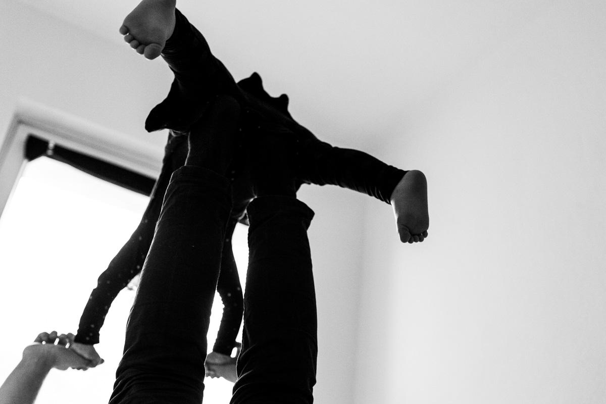 Ein Vater hält mit seinen Füßen und Händen ein Kind und lässt es in der Luft schweben.