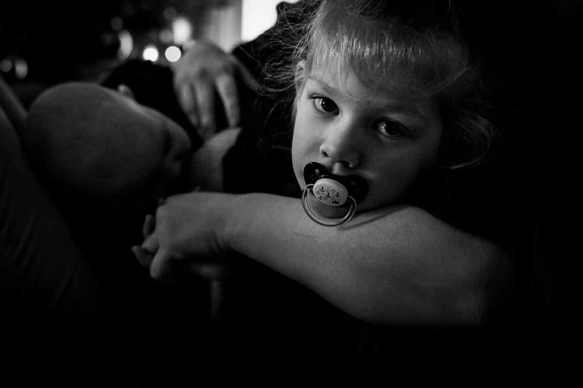 Ein größerer Junge mit einem Schnuller im Mund, er wird von der Hand seiner Mutter umarmt, die im Hintergrund stillt.