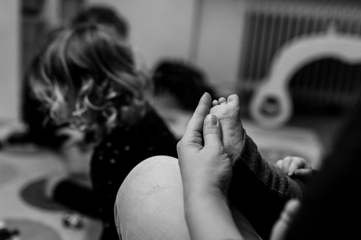 Hand einer Mutter fasst zärtlich ein Babyfuß an, im Hintergrund spielt ein kleines Mädchen.