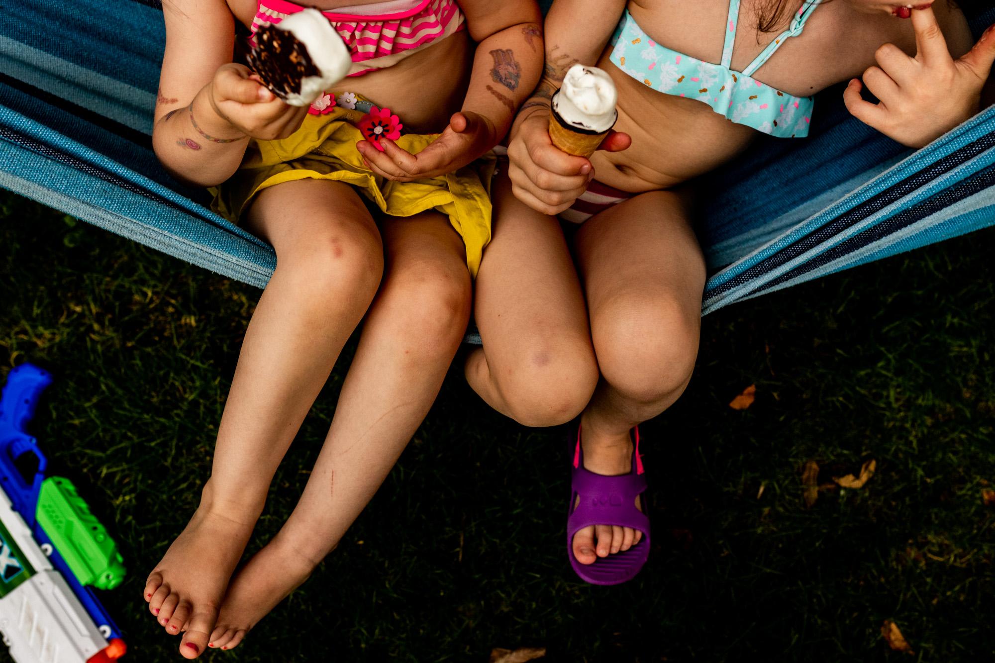 Zwei Mädchen sitzen in einer Hängematte und essen Eis.