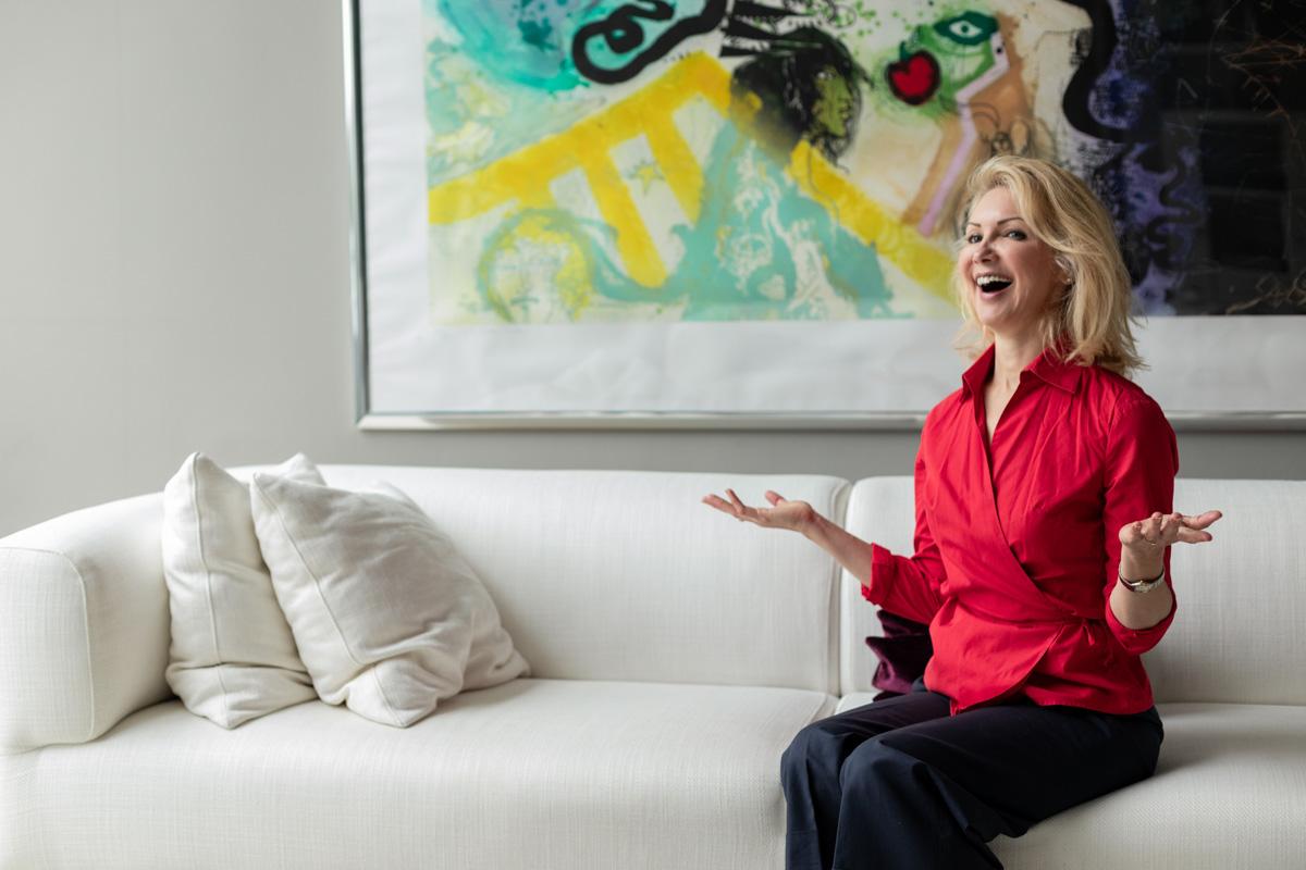 Eine Business-Frau sitzt auf einer Couch und lacht.