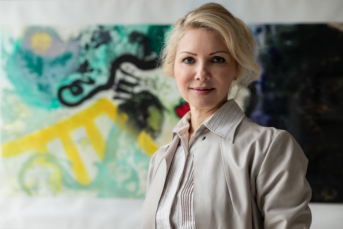 Portrait einer Business-Frau, im Hinterhgrund ein farbenfrohes Gemälde.