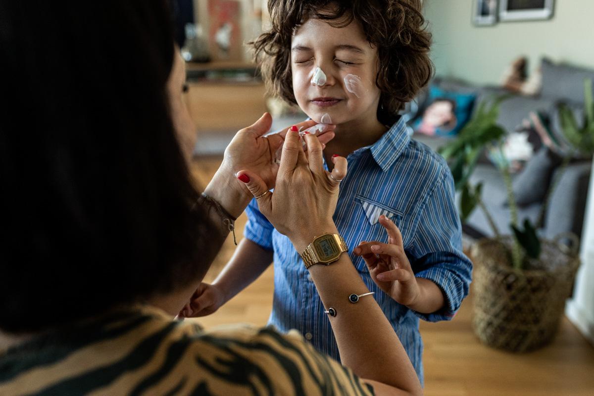 Mutter cremt ihren Sohn mit Sonnencreme im Gesicht ein.