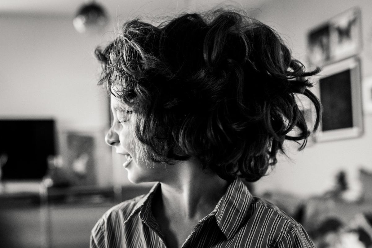 Ein Junge dreht schnell seinen Koipf, man sieht seine Haare in der Luft, schwarz-weiß Fotografie