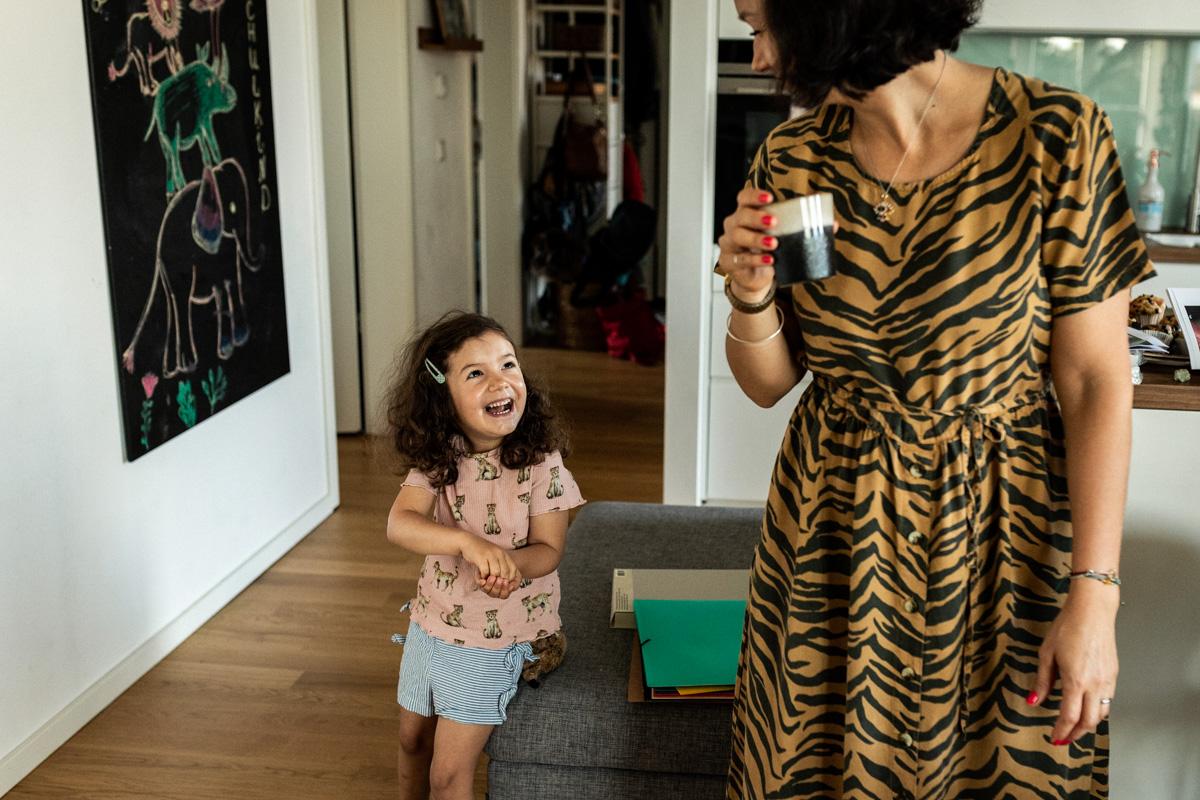 Mutter mit Tochter, Mutter hält eine Tasse in der Hand, Tochter schaut zur Mutter hoch.