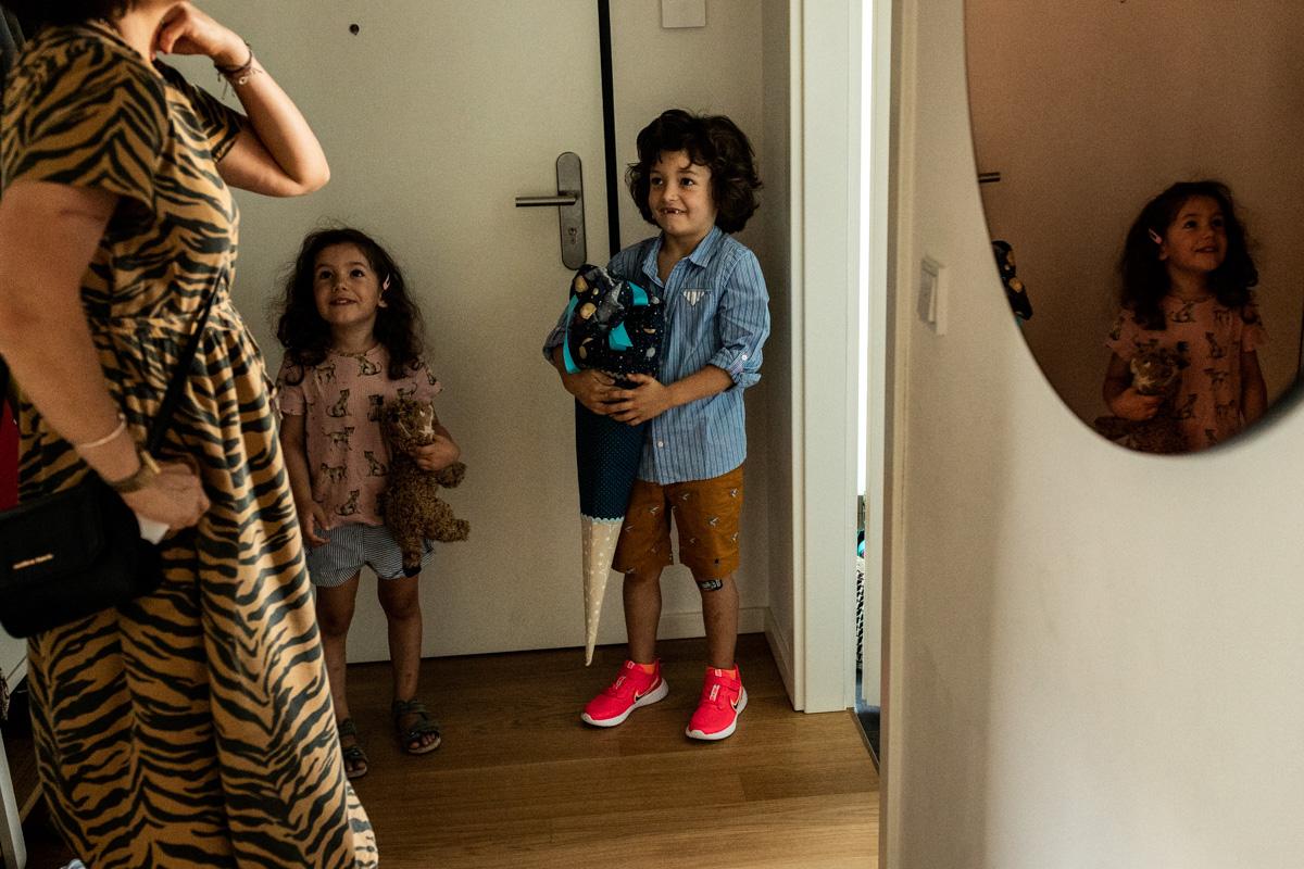 Kinder stehen vor der Tür, Junge hält eine große Schultüte in den Händen.