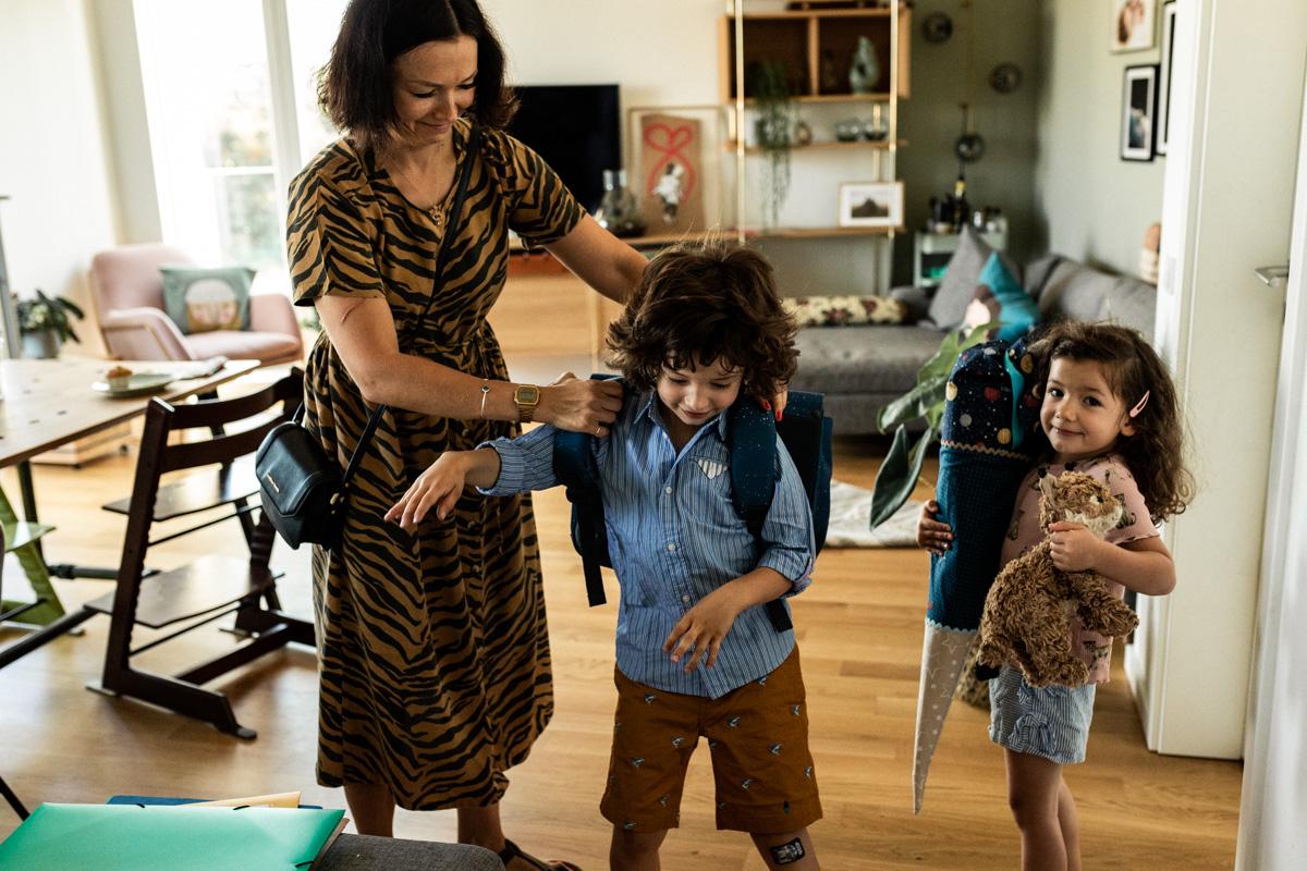Mutter hilft ihrem Sohn, den schulranzen anzuziehen, Schwester schaut zu und hält die riesige Schultüte in den Händen.