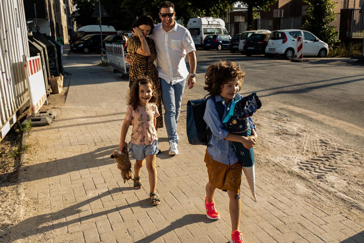 Eine Familie läuft am Einschulingstag des Sohnes zusammen zur Schule. Die Kinder sind fröhlich, die Mutter ist gerührt.